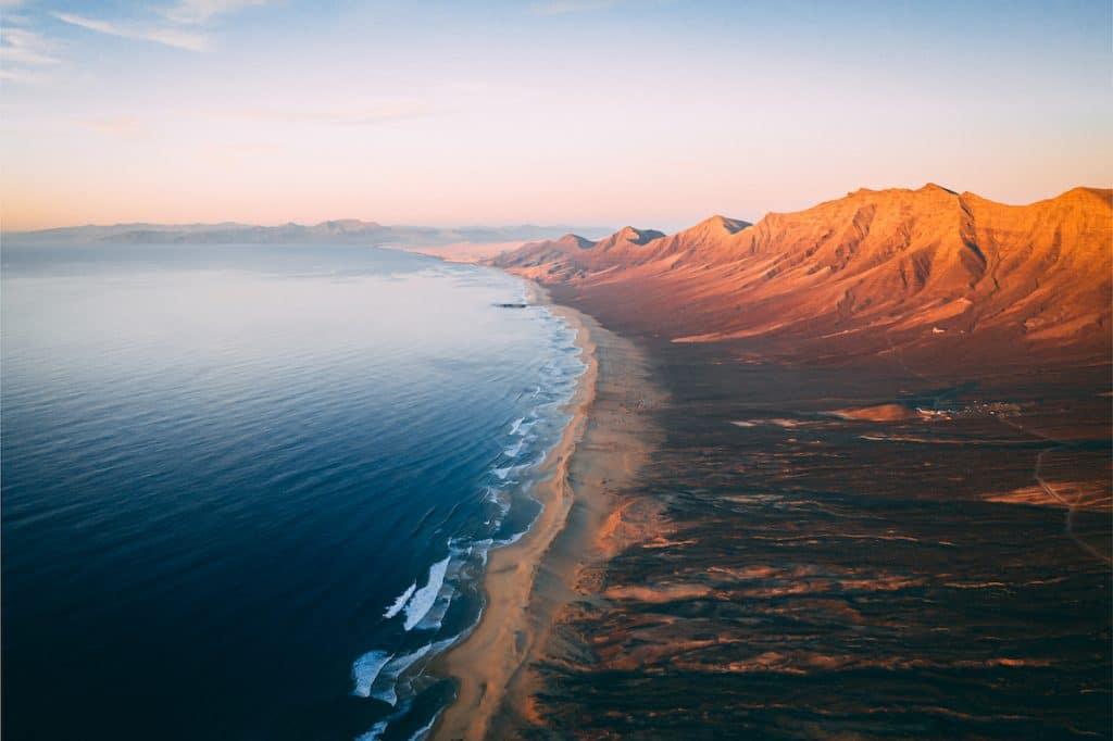 Vue aérienne panoramique de la vallée de la plage de Cofete à Fuerteventura, prise le soir au coucher du soleil.