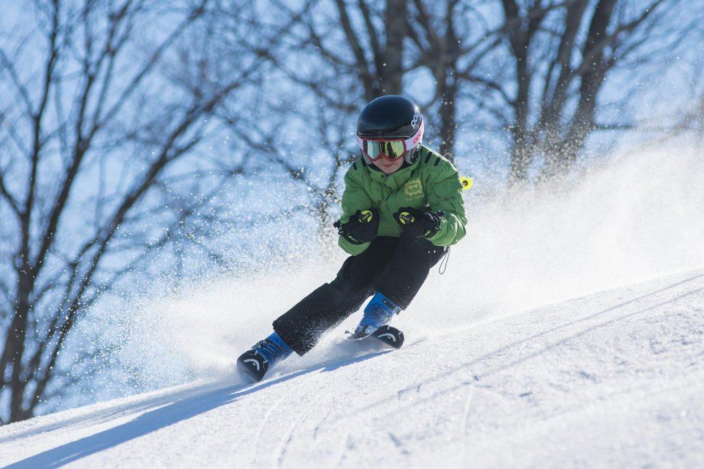 Garçon dévallant une pente à ski.