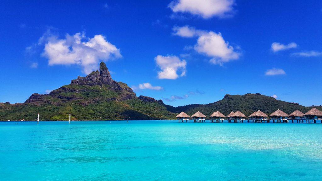 Bungalows sur pilotis dans un lagon émeraude d'une île sauvage de Polynésie.