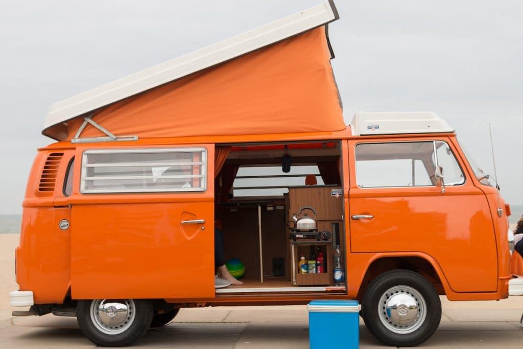 Combi Volkswagen orange et son aménagement intérieur sommaire