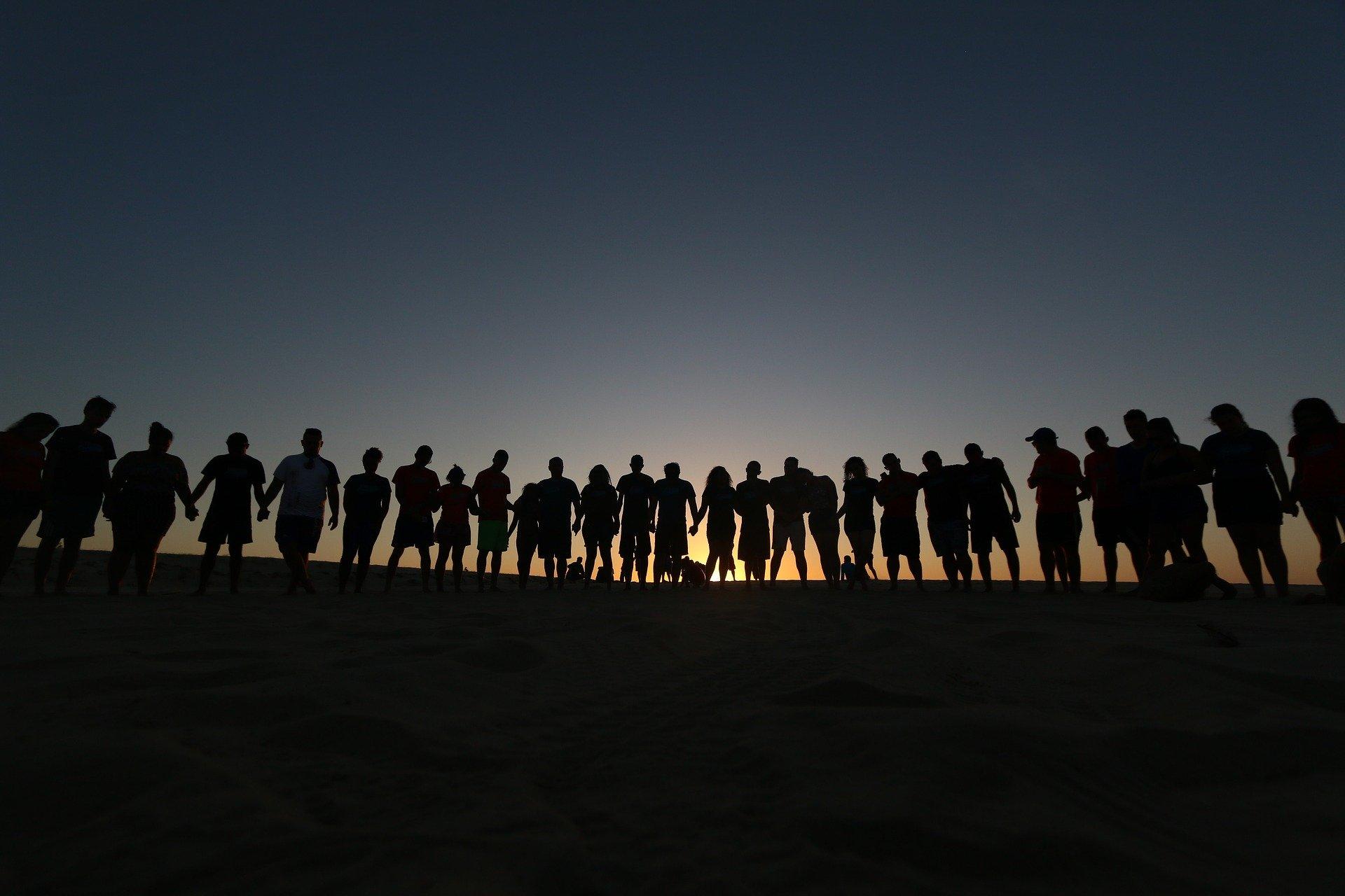 Quelque part en Europe, un groupe de personnes à la tombée de la nuit.