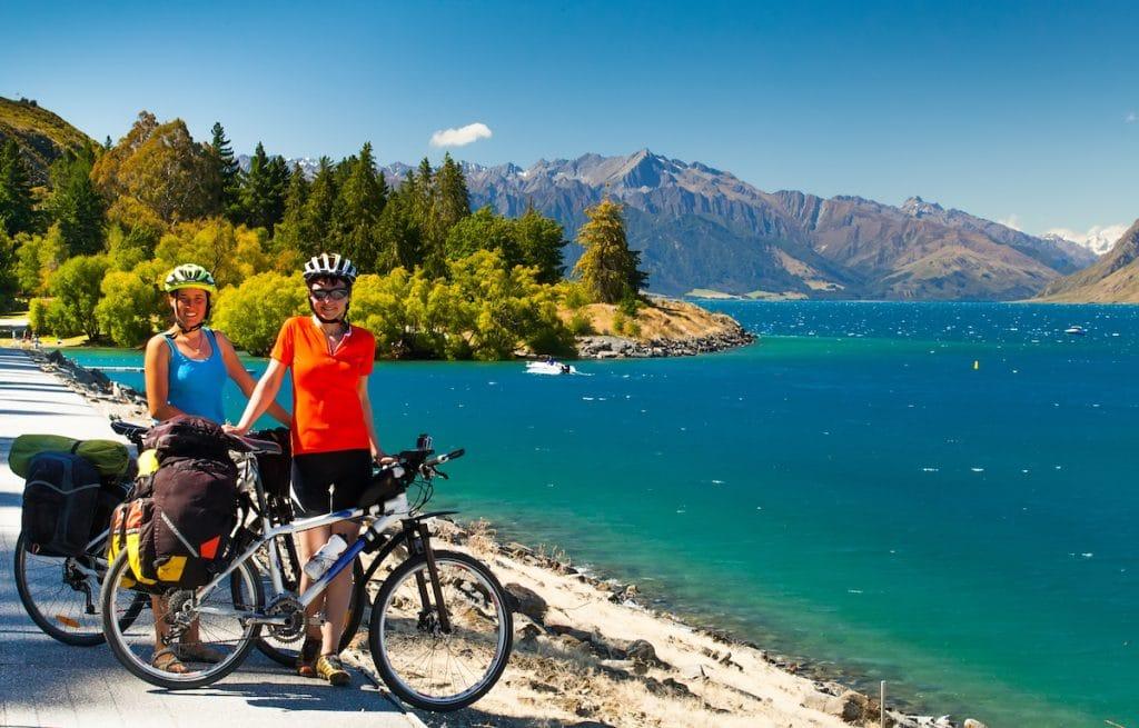Deux femmes font une pause au bord au bord d'un lac alpin pendant leur voyage à vélo.